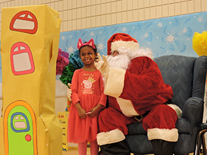 Santa Claus takes a picture with an MSD student